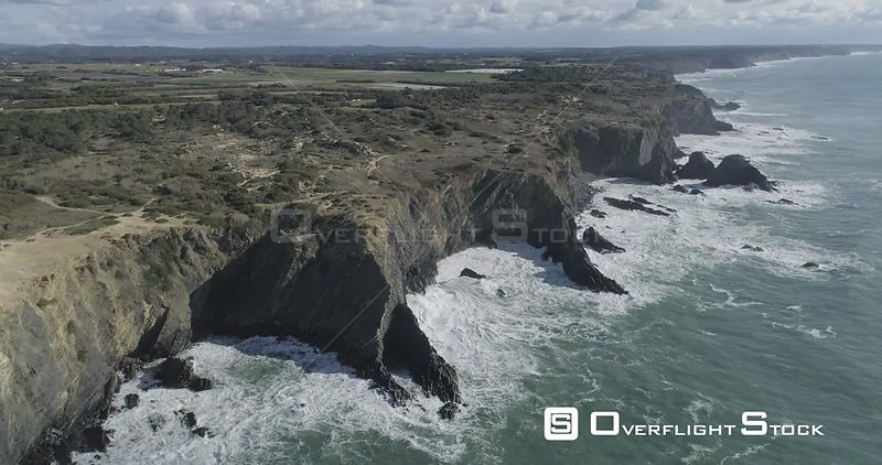 Aerial drone looking down at rocky cliffs jetting into the ocean off the coast of Portugal