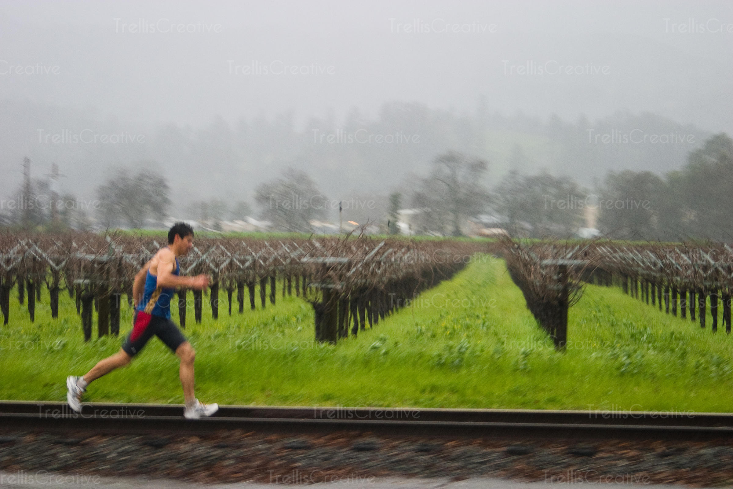 Man jogging in the rain along train tracks in Napa Valley
