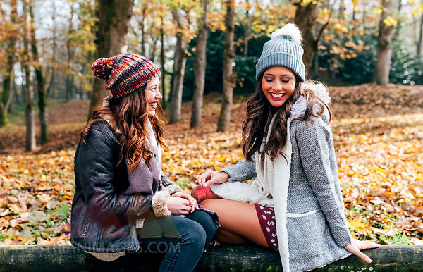 Two pretty women having fun in an autumnal forest
