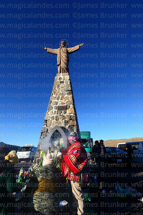 Aymara shaman or yatiri blessing clients with incense below Christ statue, La Cumbre, Cordillera Real, Bolivia