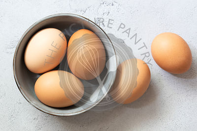 Three eggs in a bowl with two at the side.