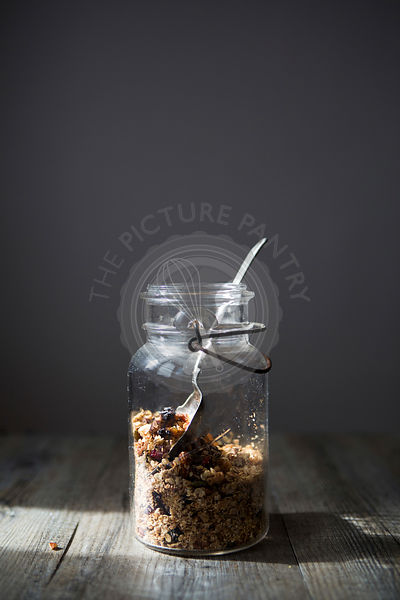 Jar of Homemade Granola with Nuts, Seeds Raisins & Cranberries with Spoon