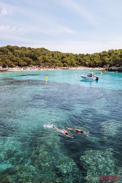 Couple snorkeling in the blue sea of Menorca, Spain