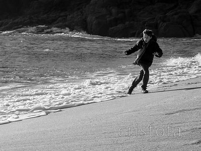 boy chased by a wave on Porthcurno Beach