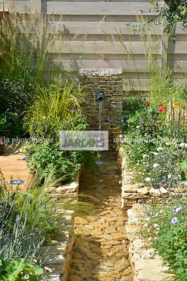 Gabion avec fontaine. Massif bordant un point d'eau. Paysagiste : Peter Reader, Hampton Court, Angleterre