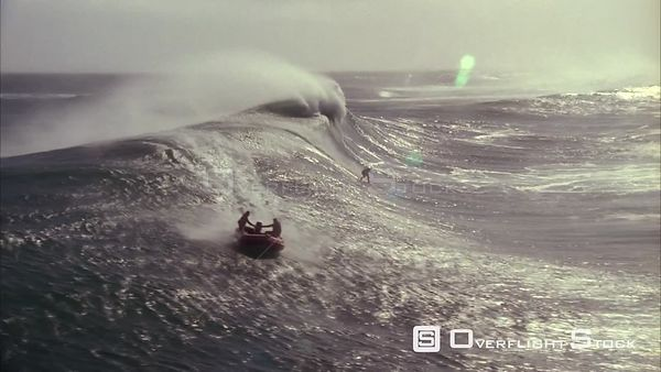 Aerial slow motion shot of a surfer riding the big waves with a dingy riding nearby. Eastern Cape South Africa