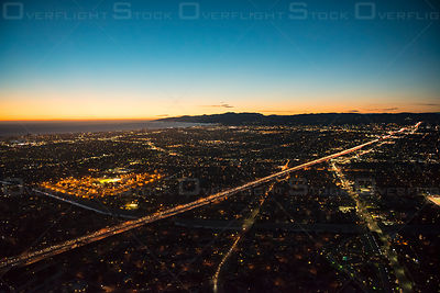 Aerial view of western Los Angeles, CA, USA, with I-405 freeway lit up by car lights cutting across the image
