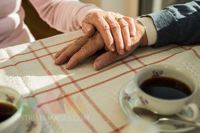 Senior couple holding hands at coffee break