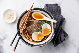 Miso Ramen Asian noodles with beef and egg in bowl on white marble background