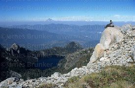 Trekker sitting on the summit of Cerro San Sebastian, Huerquehue National Park, Region IX, Chile