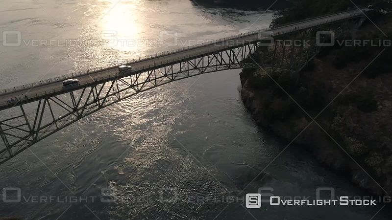Breathtaking helicopter view close to Deception Pass bridge with cars crossing the Puget Sound ocean water in Washington