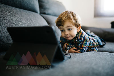 Portrait of little boy lying on the couch looking at digital tablet