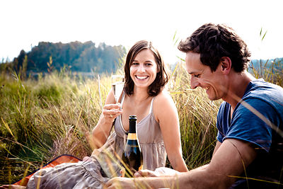 Young couple on the lakeside, drinking champagne, Bavaria, Germany