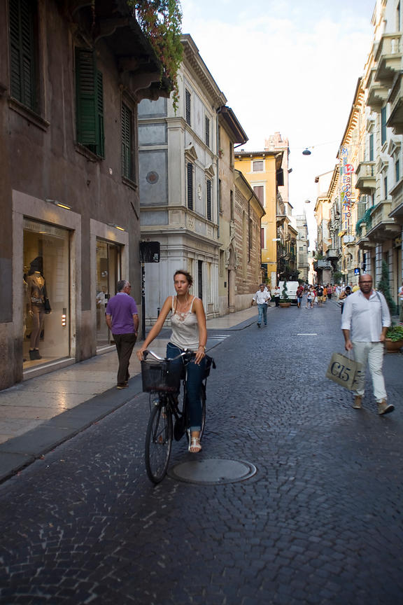 Italy - Verona - A woman rides her bicycle through the shopping streets of Verona