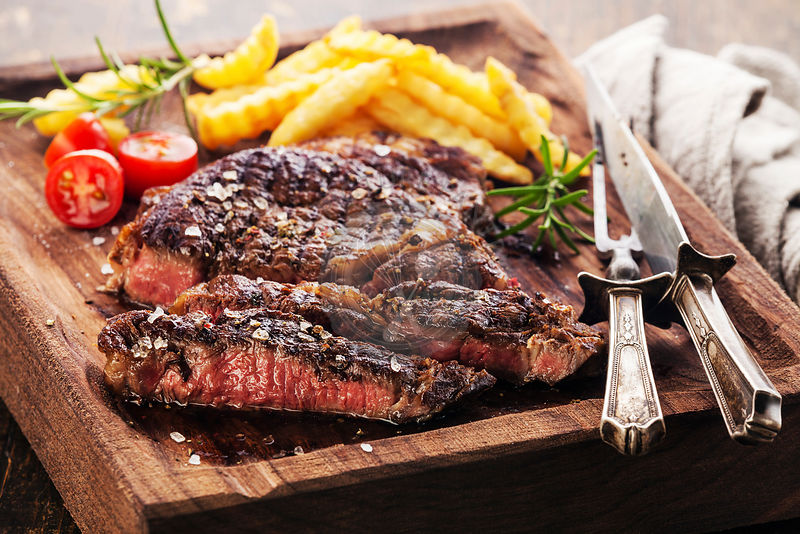 Sliced medium rare grilled Steak Ribeye Black Angus with french fries on serving board block