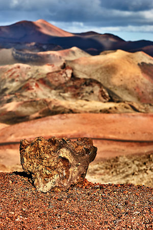 Lava rock standing against the volcanoes in the distance at Timanfaya national park, Lanzarote