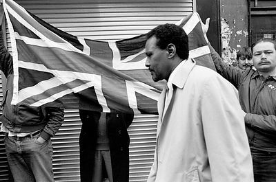 UK - London - A man walks past Fascist protesters from the National Front holding a Union Jack Flag