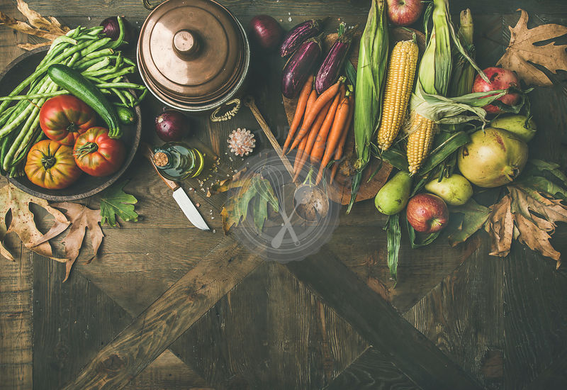 Flat-lay of green beans, corn cobs, carrot, tomatoes, eggplants, fruits and fallen leaves over wooden table, top view, copy space