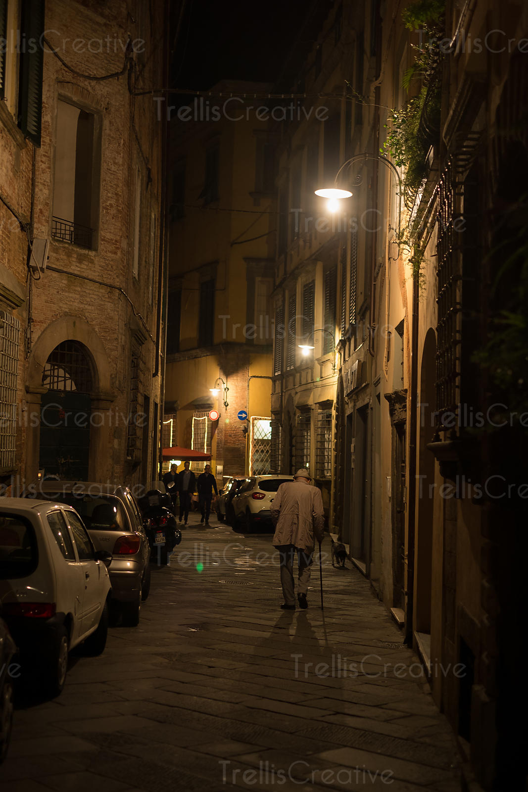 Elderly man walking down and alley at night in Lucca, Italy