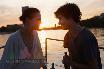 Germany, Berlin, Young couple on boat, holding bottles, side view, portrait