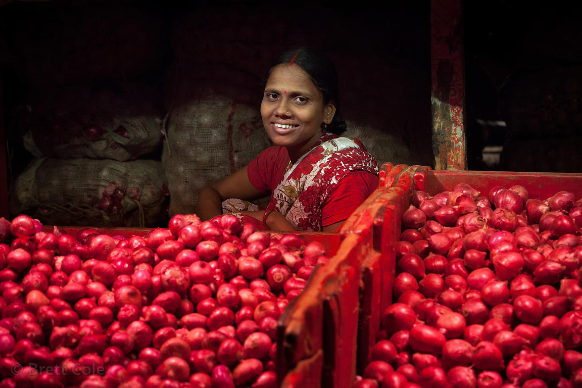 A woman sells onions under red lights (to enhance the appearance) at Kole vegetable market, Bowbazar, Kolkata, India.