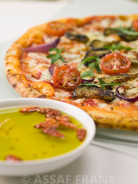 Close-up of pizza and olive oil in bowl