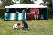 UK - Standon - A mother and her child eat a takeway meal on the ground at the Standon Calling Festival