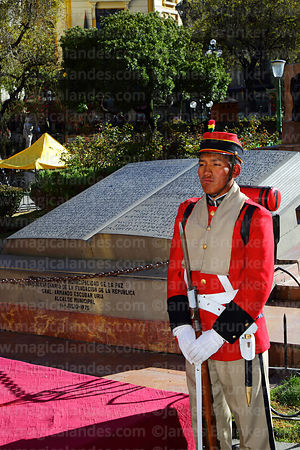 A members of the Los Colorados regiment stands in front of a carved stone book with text of the Proclamation of the Junta Tuitiva in Plaza Murillo during events to commemorate the uprising of July 16th 1809, La Paz, Bolivia