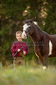 boy standing with pony