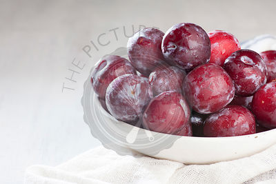 Washed Ripe Plums on white rustic background