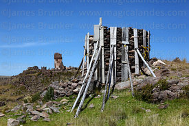 Wooden supports around rough stone chulpa to prevent it collapsing, Sillustani, Peru