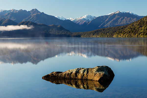 Sunrise over Lake Kaniere near Hokitika with perfect reflections and Toaroha Ranges in background, West Coast, South Westland...