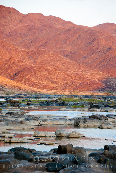 The Orange River flows through arid desert mountains lit by the rising sun.