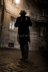 An atmospheric image of a shadowy man with a hat walking through the streets of an old town at night.
