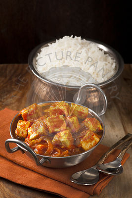 Paneer and sweet pepper curry with rice on wooden background