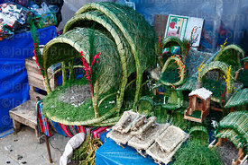 Grass and plastic stables and mangers for nativity scenes for sale in Christmas market, La Paz, Bolivia