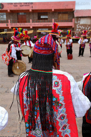 Male dancer wearing braids made from the hair of his wife at San Santiago festival , Taquile Island , Peru