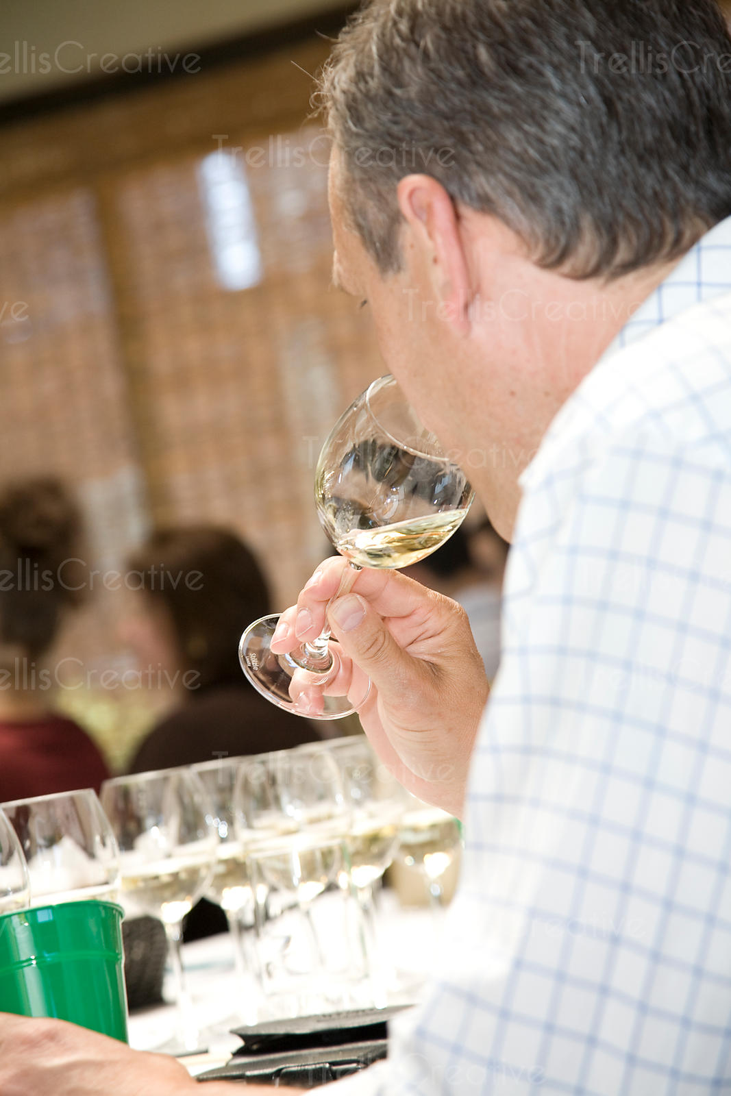 A middle aged man smells white wine at tasting