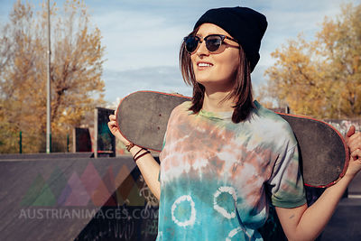 Smiling young woman holding skateboard at skatepark