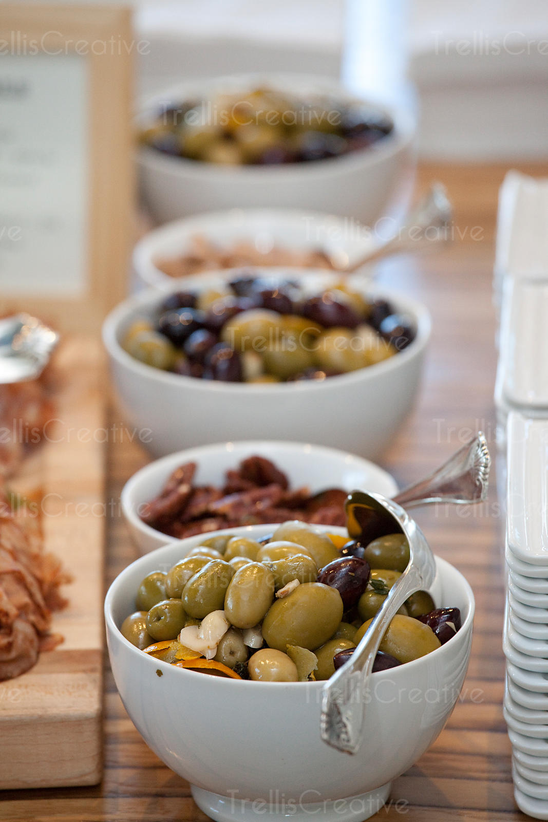 White bowls filled with various marinated olive varieties