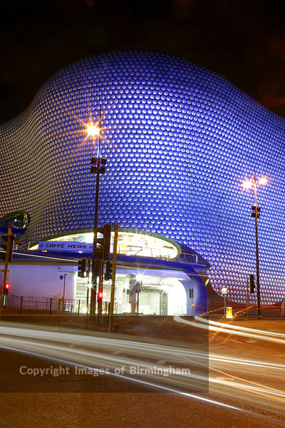 The Selfridges shop building at the Bullring Shopping Centre in Birmingham, England, UK.  The whole development has been the source of much debate thanks to its unusual architecture.  Pictured at night with trails of light from traffic.