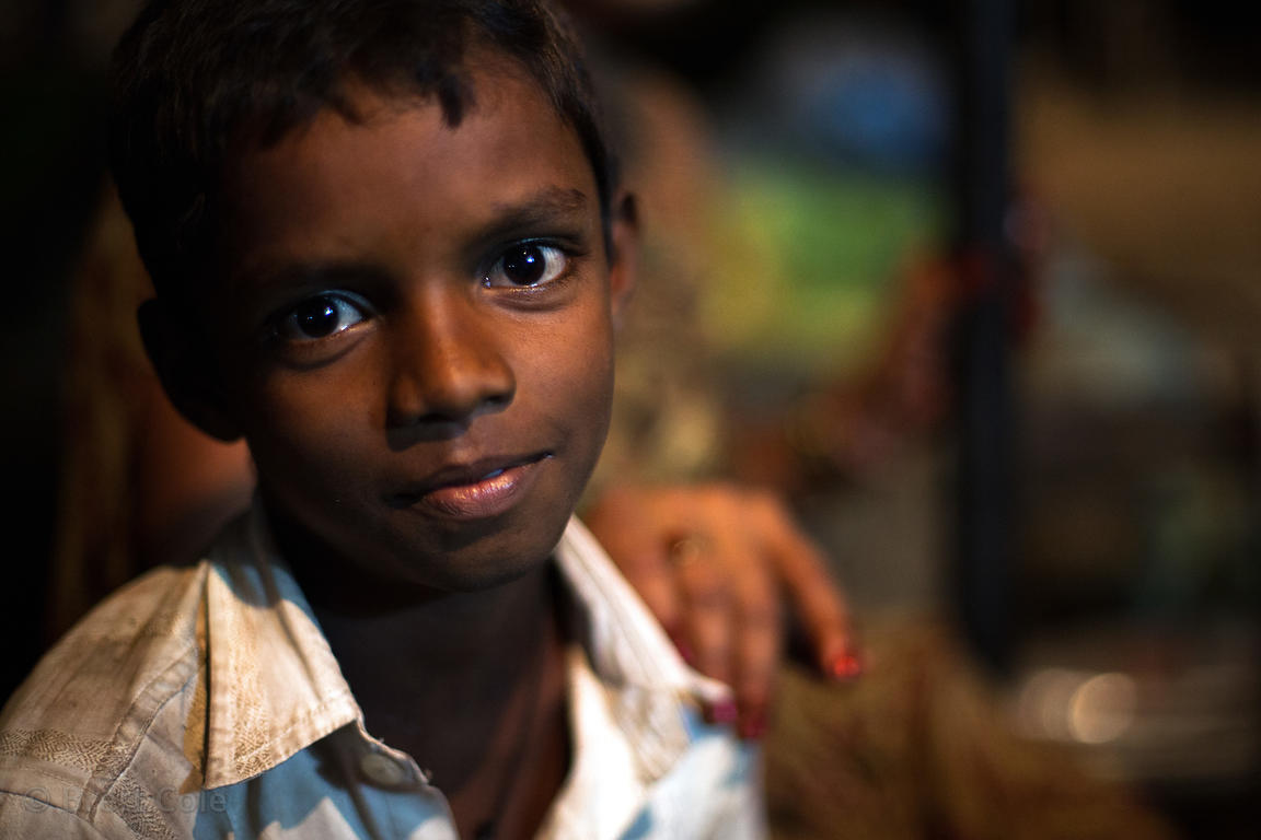 Nighttime portrait of a boy selling fish in the Kokri Agar slum, Mumbai, India.