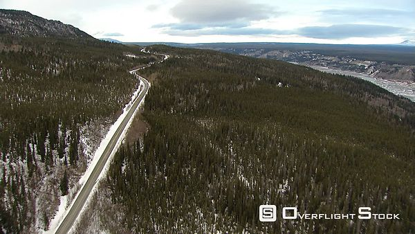 Flying above forest and highway in Alaska