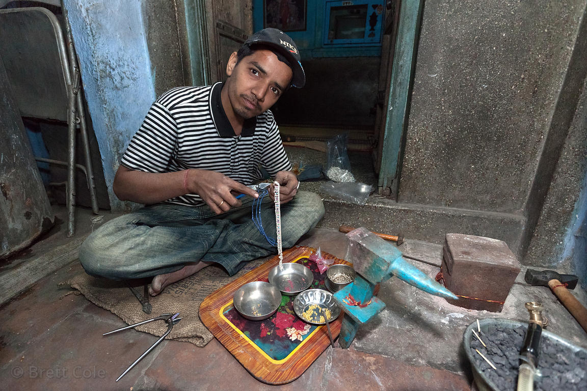 A craftsman fastens stone to silver bracelets, Jodhpur, Rajasthan, India