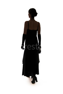 A silouette of a vintage 1920s - 1930s woman in a long black dress with gloves – shot from eye level.