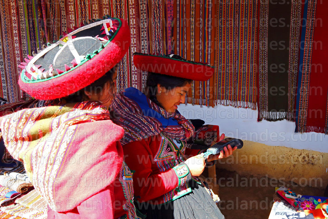 Quechua woman wearing traditional dress processing credit card in textile shop, Chinchero, Sacred Valley, Cusco Region, Peru