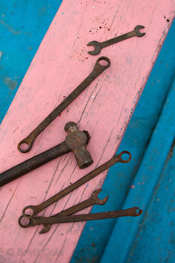 Old tools on the deck of a pastel painted fishing boat on Chowpatty Beach, Mumbai, India.