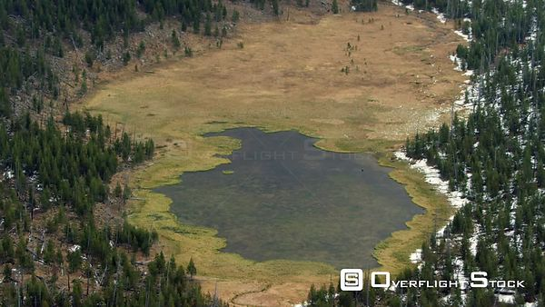 A mountain lake sits in a meadow in on the western edge of Yellowstone National Park
