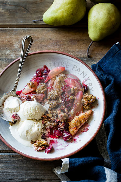 Cranberry pear crisp with ice cream on a wooden background