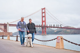 2 caucasion adult men walking a large sheepadoodle puppy in front of the golden gate bridge in San Francisco